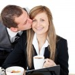Young businessman kissing his delighted girlfriend — Stock Photo