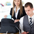 Royalty-Free Stock Photo: Businesswoman packing her bag businessman using laptop
