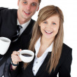 Happy couple of business holding a coup smiling at the camera — Stock Photo