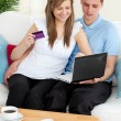 Happy couple using a laptop to buy online — Stock Photo