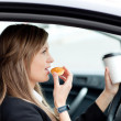 Charming businesswoman eating and holding a drinking cup while d — Stock Photo #10824925