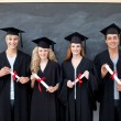 Group of adolescents celebrating after Graduation - Stock Photo