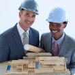Smiling engineers with hard hats holding a model house — Stock Photo