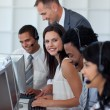 Businesswoman in a call center with her team and manager — Stock Photo #10825058