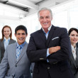 Stock Photo: Senior manager with folded arms accompanied by his team