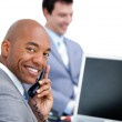 Happy businessman on phone and his colleague working at a comput — Stock Photo #10825111