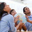 Foto Stock: International business team holding terrestrial globe