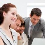 Портрет улыбаясь бизнесвумен, работать с ее коллегами — Стоковое фото