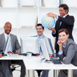 Stock Photo: Smiling manager holding a globe with his team working at compute