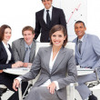 Assertive female executive sitting in front of her team — Stock Photo