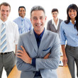 Royalty-Free Stock Photo: Smiling manager with folded arms in front of his team