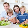 Cheerful young family cooking together — Stock Photo
