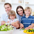 图库照片: Cheerful young family cooking together