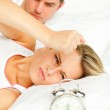 Man and angry woman in bed looking at the alarm clock going off — Stock Photo #10825483