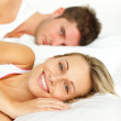 Couple resting in bed and woman smiling at the camera — Stock Photo