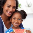 Smiling mother and her daughter eating fruit — Stock Photo