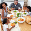 Smiling family dining together — Stockfoto