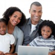 Photo: Happy Afro-American family using a laptop in the living-room