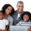 Foto Stock: Happy Afro-American family using a laptop in the living-room