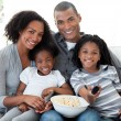 Afro-American family watching television at home — Stockfoto