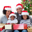 Afro-American family holding Christmas presents — Stock Photo