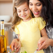 Brunette mother helping her daughter prepare salad — Stock Photo #10825656