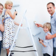 Stock Photo: Happy family painting a room with brushes