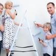 familia feliz pintando una habitación con cepillos — Foto de Stock