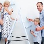lycklig familj måla ett rum med penslar — Stockfoto