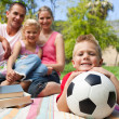 Stock Photo: Little boy having fun with a soccer ball with his family smiling