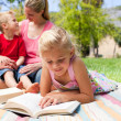 Concentrated blond girl reading while having a picnic with her f — Stok fotoğraf