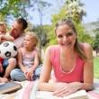 Smiling woman reading at a picnic with her family — Stock Photo #10825721