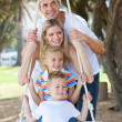 Stock Photo: Cheerful family swinging