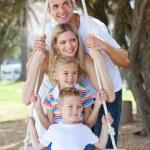 Cheerful family swinging — Stock Photo #10825728