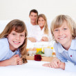 Jolly family having breakfast sitting on bed — Stock Photo #10825752