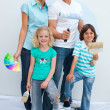 Happy family decorating their new house — Stock Photo