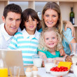 Joyful family using laptop during the breakfast — Stock Photo