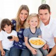 Loving family watching television sitting on sofa — Stockfoto
