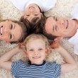Smiling young family lying on the floor — Stock Photo