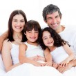 Royalty-Free Stock Photo: Portrait of a happy family sitting on a bed