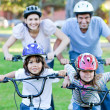 Happy family riding a bike — Stock fotografie