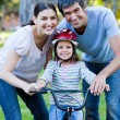 Little girl learning to ride a bike with her parents — Stock Photo #10825811