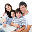 Happy family using a laptop sitting on sofa — Stock Photo