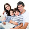 Happy family using a laptop sitting on sofa — Stock Photo #10825819