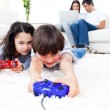 Excited children playing video games lying on the floor — Stock Photo #10825824