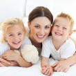 Happy mother and her children lying on a bed — Stock Photo #10825828