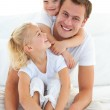 Caring father with his children sitting on bed — Stock Photo
