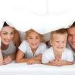 Young family playing together on a bed — Stock Photo