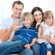 Smiling young family singing a karaoke together — Stock Photo #10825886