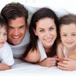 Royalty-Free Stock Photo: Portrait of a smiling family lying on bed